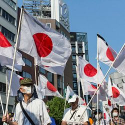 Demonstrators hold Japanese national flags as they march during a protest in support of the Yasukuni Shrine on August 15, 2020 in Tokyo, Japan. (Image by Yuichi Yamazaki/Getty Images News/Getty Images)