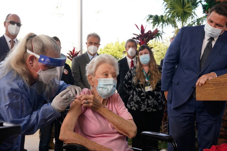 Florida Gov. Ron DeSantis watches as nurse Christine Philips, left, administers the Pfizer-BioNTech vaccine for COVID-19 to Vera Leip, 88, a resident of John Knox Village, Wednesday, Dec. 16, 2020, in Pompano Beach, Fla. Nursing home residents and health care workers in Florida began receiving the vaccine this week. (AP Photo/Marta Lavandier)